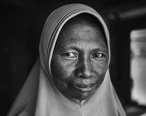 A 28mm wide angle black and white portrait of a smiling hijabi woman from Rainbow Village, Tual, Maluku, Indonesia