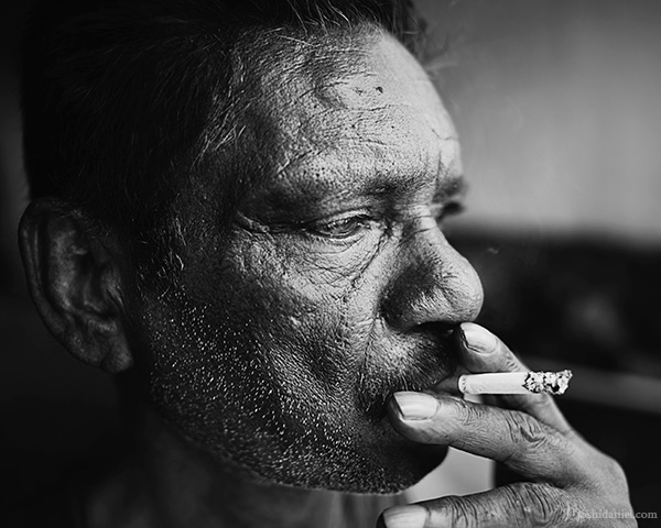 A 28mm wide angle black and white portrait of a of a man smoking cigarette