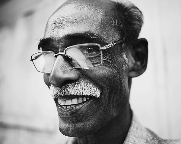 A 28mm wide angle black and white portrait of a bespectacled smiling man from Trivandrum, Kerala, India