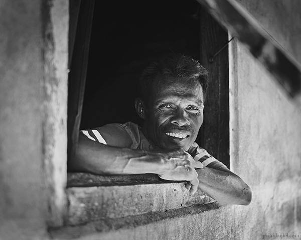 A 28mm wide angle black and white portrait of a man curiously looking out of a window in Tual, Maluku, Indonesia