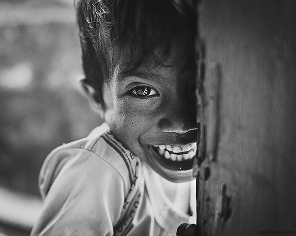 A 28mm wide angle black and white portrait of a laughing young boy from Rainbow Village, Tual, Maluku, Indonesia