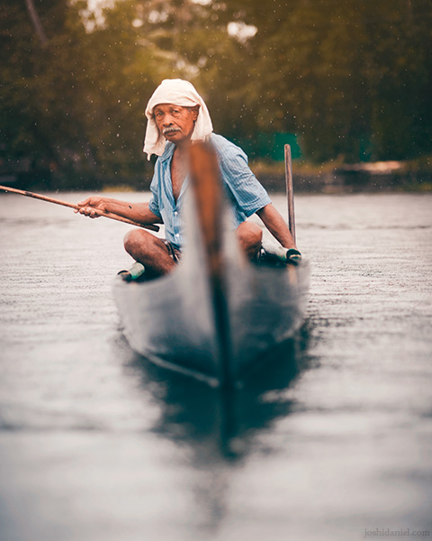 An old man fishing out of his boat on a rainy day in Alappuzha, Kerala, India