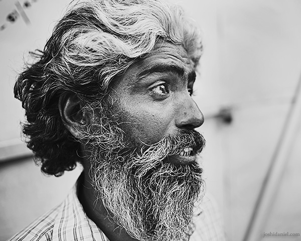 A 28mm wide angle black and white portrait of a bearded man talking in Trivandrum, Kerala, India