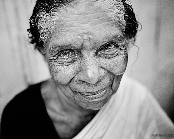 A 28mm wide angle black and white portrait of smiling old woman in Trivandrum, Kerala, India