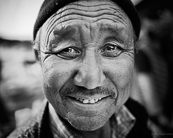 A 28mm wide angle black and white portrait of smiling Dorjee, the owner of a dhaba in Batal, Spiti Valley, Himachal Pradesh, India