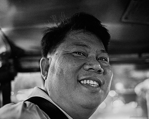 A 28mm wide angle black and white portrait of a smiling jeepney driver in Manila, Philippines