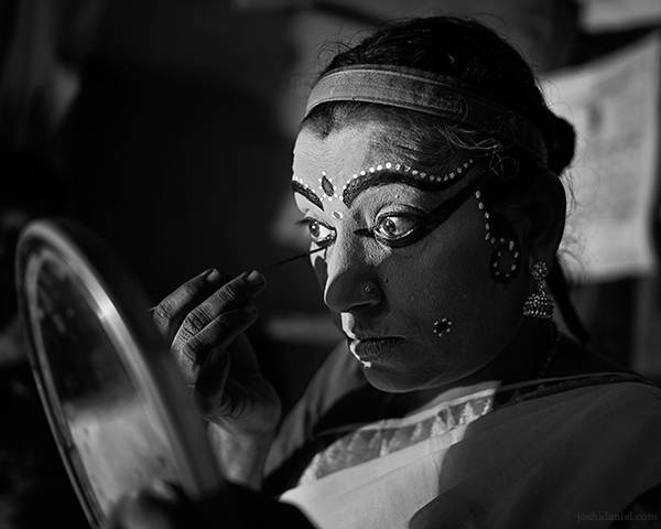 A 28mm wide angle black and white portrait of Nangiarkoothu artist Margi Usha doing make-up in Trivandrum, Kerala, India