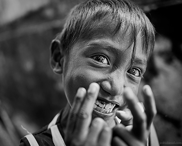 A 28mm wide angle black and white portrait of a young, grinning boy from Rainbow Village, Tual, Maluku, Indonesia