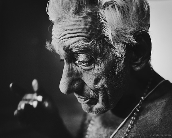 A 28mm wide angle black and white portrait of Kathakali artist Nelliyode Vasudevan Namboodiri doing make-up in Trivandrum, Kerala, India