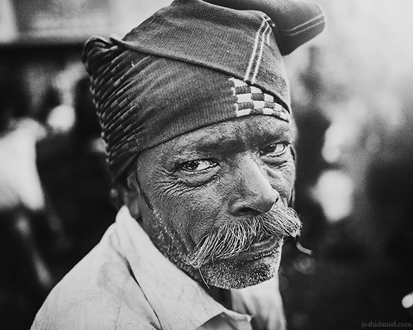 A 28mm wide angle black and white portrait of a street vendor from K. R. Market, Bangalore, Karnataka, India