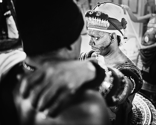 A 28mm wide angle black and white portrait of a Muthappan Theyyam performer getting ready in Kannur, Kerala, India
