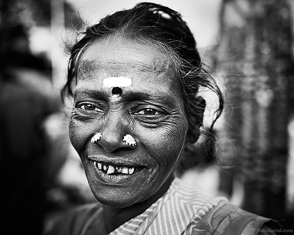 A 28mm wide angle black and white portrait of a smiling flower seller from K. R. Market, Bangalore, Karnataka, India