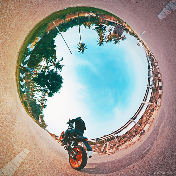 Inverted little planet (tiny planet) self-portrait of joshi daniel pulling a wheelie on KTM Duke in Bangalore Rural, Karnataka, India