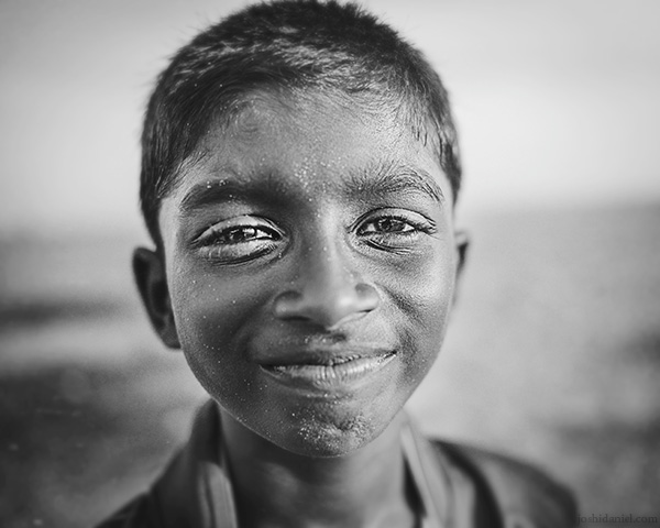 A 28mm wide angle black and white portrait of a smiling boy from Trivandrum, Kerala, India