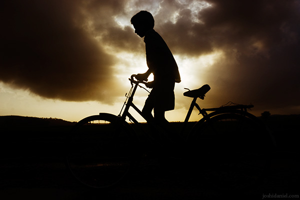 A boy cycling on a cloudy day in Hegde, Kumta, Karnataka, India
