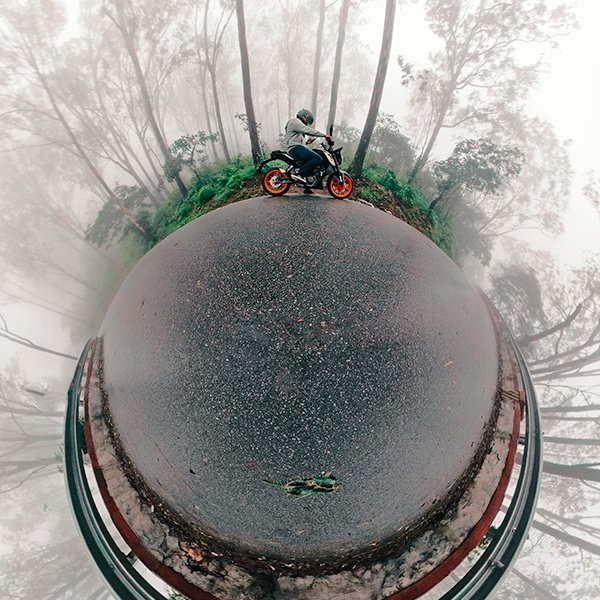 Little planet (tiny planet) self-portrait of joshi daniel on a KTM Duke in Nandi hills, Karnataka, India on a foggy day
