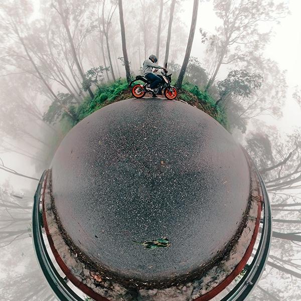 Little planet (tiny planet) self-portrait of joshi daniel on a KTM Duke in Nandi hills, Karnataka, India on a foggy day