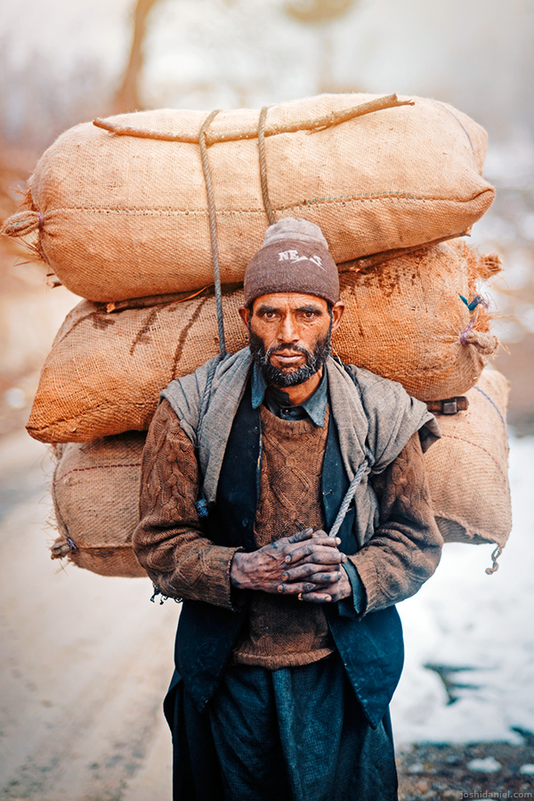 Portrait of a man carrying heavy load on his back in Anantnag, Jammu and Kashmir, India